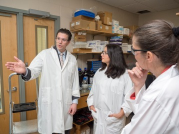 Dr. Eric Price gives the ministers a tour of his lab